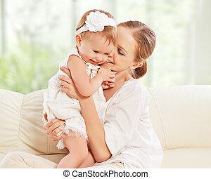 feliz, family., mãe bebê, filha, jogos, abraçando, beijando, casa, sofá