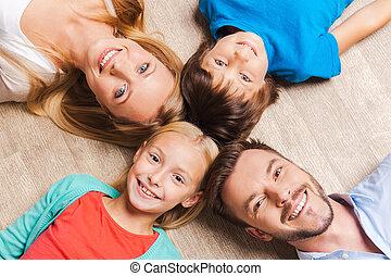 feliz, family., punta la vista, de, familia feliz, de, cuatro, vinculación, a, uno al otro, cabezas, y, sonriente, mientras, acostado, en, el, piso madera dura
