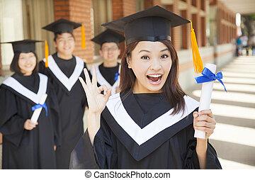 feliz, graduado faculdade, segurando, diploma, e, fazer, um, gesto