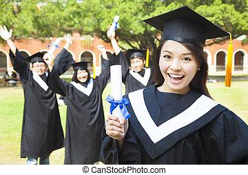 feliz, graduado faculdade, segurando, um, diploma, com, amigos