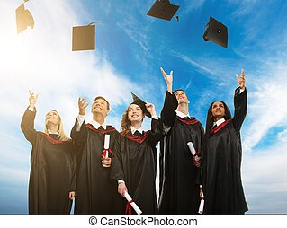 feliz, grupo multi étnico, de, graduado, jovem, estudantes, chapéus lançando ar