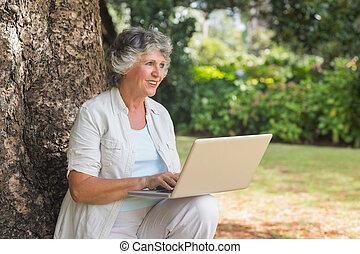 feliz, haired gris, mujer, con, un, computador portatil, sentado, en, árbol