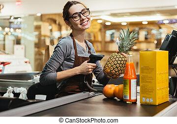 feliz, hembra, cajero, exploración, tienda de comestibles, artículos