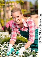 feliz, hembra, trabajador, en, centro de jardín, flores