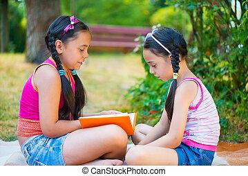 feliz, hispano, hermanas, lectura, en el parque