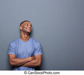 feliz, hombre africano, reír, con, armamentos cruzaron