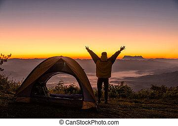 feliz, hombre, con, brazos abiertos, estancia, cerca, tienda, alrededor, montañas, debajo, salida del sol, luz, cielo, el gozar, el, ocio, y, freedom.