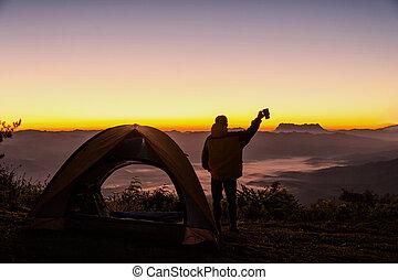 feliz, hombre, con, sostener la taza de café, estancia, cerca, tienda, alrededor, montañas, debajo, salida del sol, luz, cielo, el gozar, el, ocio, y, freedom.