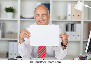 feliz, hombre de negocios, tenencia, blanco, papel, en el escritorio
