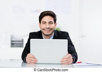 feliz, hombre de negocios, tenencia, computador portatil, en el escritorio