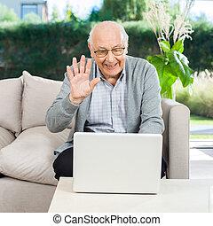 feliz, hombre mayor, vídeo, charlar, en, computador portatil