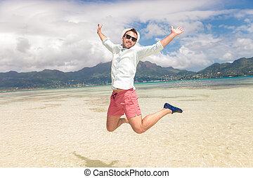 feliz, homem jovem, pular, de, alegria, praia
