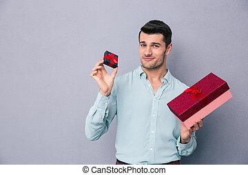 feliz, homem jovem, segurando, pequeno, e, presente grande, caixa