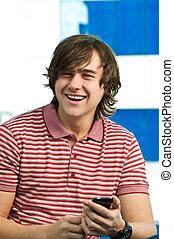 feliz, homem jovem, usando, telefone móvel, olhando câmera