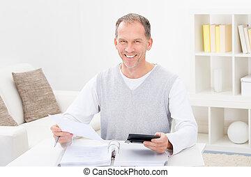 feliz, homem maduro, segurando, calculadora, e, contas
