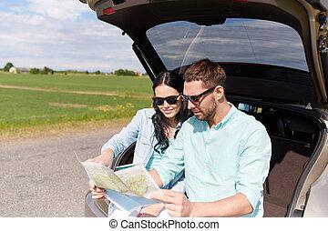 feliz, homem mulher, com, mapa estrada, em, carro hatchback