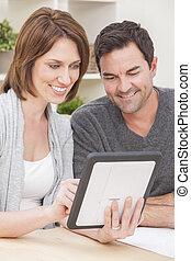 feliz, homem, &, mulher, par, usando, tabuleta, computador, casa