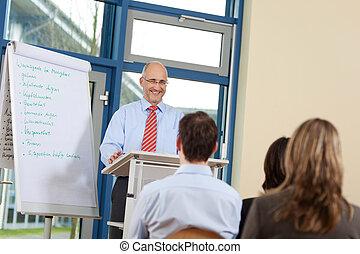 feliz, homem negócios, dar, apresentação, para, coworkers, enquanto, ficar, em, pódio, em, escritório