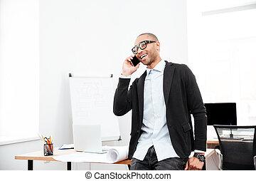 feliz, homem negócios, falando, ligado, a, telefone pilha, em, escritório