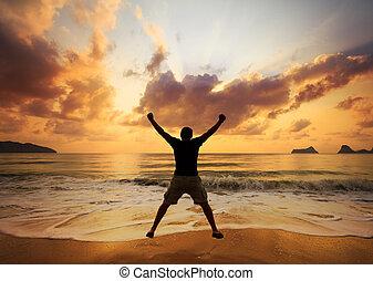 feliz, homem saltando, sobre, sea., praia areia, em, dawn.