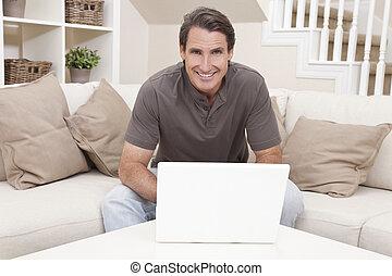 feliz, homem usa laptop, casa