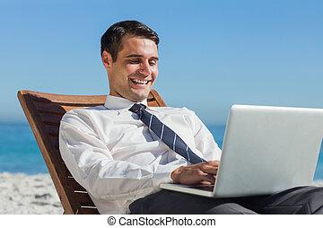 feliz, jovem, homem negócios, ligado, um convés, cadeira, usando, seu, computador