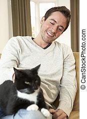 feliz, joven, con, gato que sienta, en, sofá