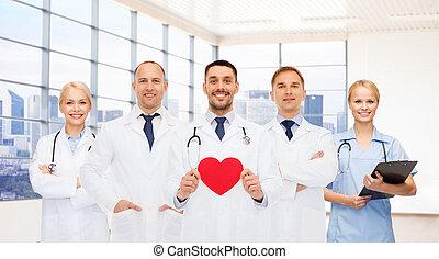 feliz, joven, doctors, cardiólogos, con, corazón rojo