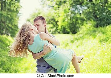 feliz, joven, dulce, pareja, es, besar, hombre y mujer, enamorado, él, asideros, ella, en, un, manos, en, pasto o césped, aire libre