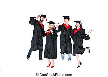 feliz, joven, estudiantes, en, casquillos de la graduación, con, diplomas, saltar, aislado, blanco