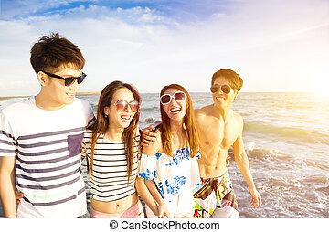 feliz, joven, grupo, ambulante, en la playa, en, vacaciones del verano