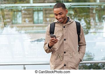 feliz, joven, hombre africano, charlar, aire libre