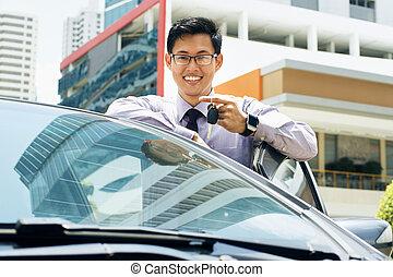 feliz, joven, hombre asiático, sonriente, actuación, llaves, de, coche nuevo