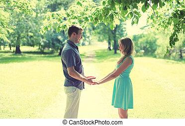 feliz, joven, sonriente, pareja, enamorado, asideros, manos, relaciones, fecha, boda, -, concepto, vendimia, colores suaves, soleado, silueta, en, parque