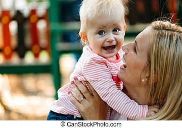 feliz, mãe bebê, beijando, rir, e, abraçando, em, natureza, ao ar livre