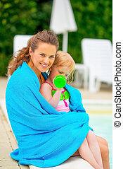 feliz, mãe bebê, menina, embrulhado toalha, sentando, em, poolside