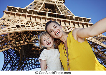 feliz, mãe criança, levando, selfie, frente, torre eiffel