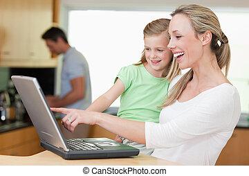 feliz, mãe filha, usando computador portátil, junto, com, pai, em, a, fundo