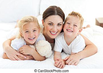 feliz, madre, y, ella, niños, acostado, en, un, cama