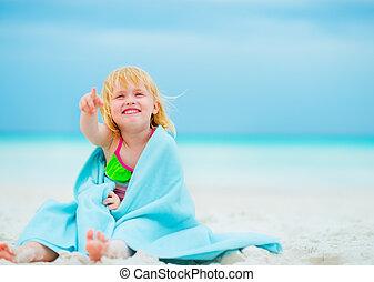 feliz, menina bebê, em, toalha, sentando praia, e, apontar, ligado, cópia, s