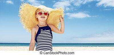 feliz, menina, em, listrado, swimsuit, e, grande, chapéu palha, branco, praia