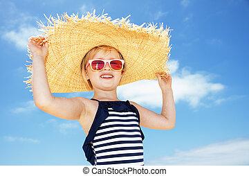 feliz, menina, em, swimsuit, e, grande, chapéu palha, contra, céu azul