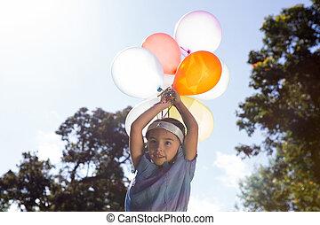 feliz, menininha, segurando, balões