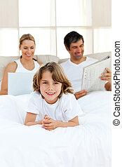 feliz, menino, com, seu, pais, relaxante, em, a, fundo