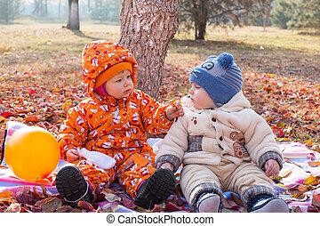 feliz, menino criança, e, menina, tocando, com, folhas, em, outono, park., a, conceito, de, infancia, e, fall.