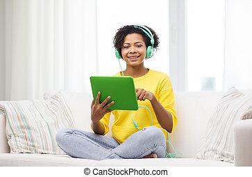 feliz, mujer africana, con, computadora personal tableta, y, auriculares