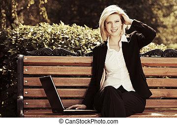 feliz, mujer de negocios, con, computador portatil, en, un, parque de la ciudad