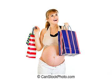 feliz, mujer embarazada, tenencia, bolsas de compras, en, manos, aislado, blanco