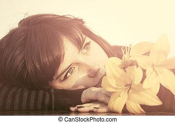 feliz, mujer joven, con, flores, soñar despierto, al aire libre