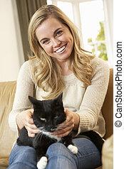 feliz, mujer joven, con, gato que sienta, en, sofá